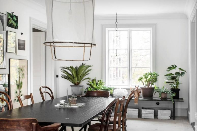 The dining space shows off a gallery wall,  stylish vintage dining set and some books