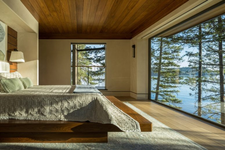 The master bedroom features an almost glazed wall and severla large windows, all done for amazing views