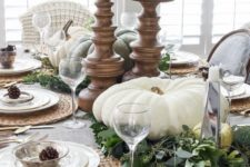 07 a neutral table setting with large white pumpkins and candles, pinecones, fresh greenery and woven placemats