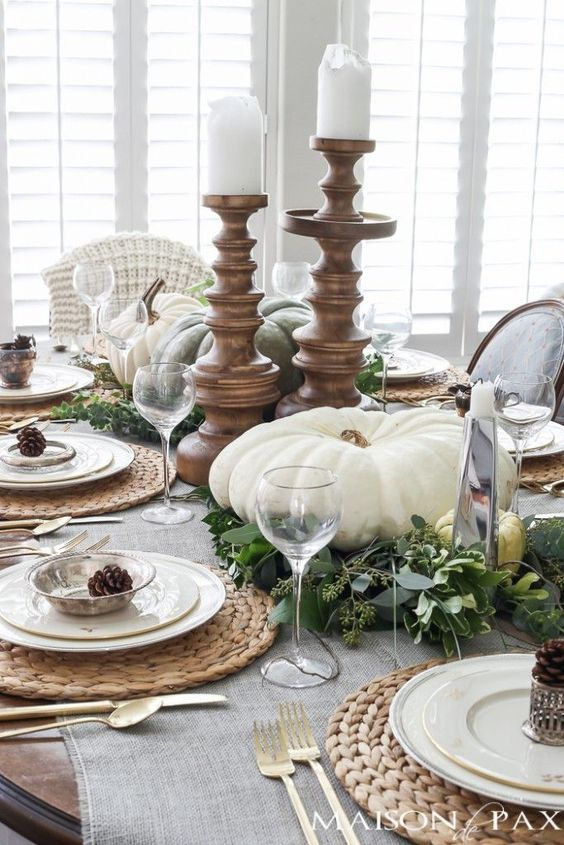 a neutral table setting with large white pumpkins and candles, pinecones, fresh greenery and woven placemats