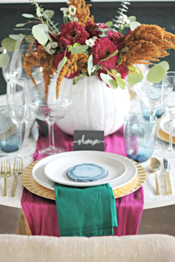 pink and emerald textiles and a bold floral centerpiece with pink and mustard blooms and greenery