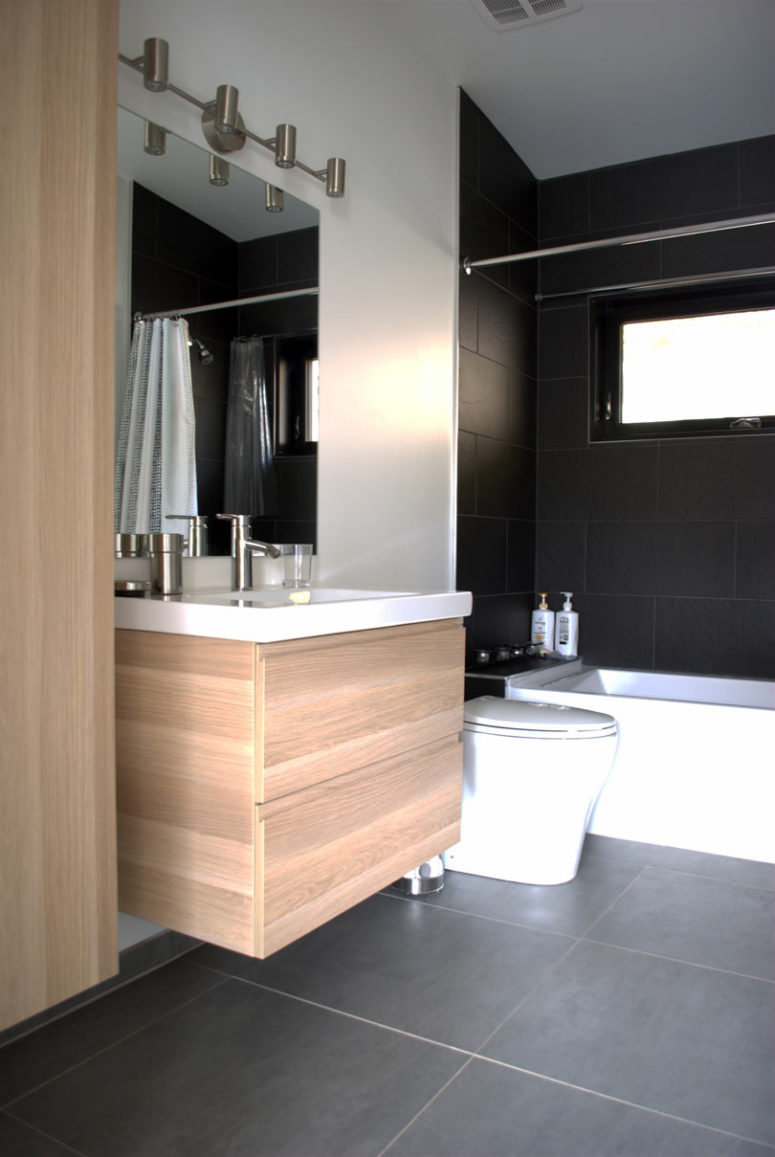 The bathroom is done in minimalist style, just like the rest of the house and features the same materials in decor