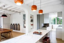 08 The kitchen features minimalist cabinets, a large kitchen island and a vintage dining set
