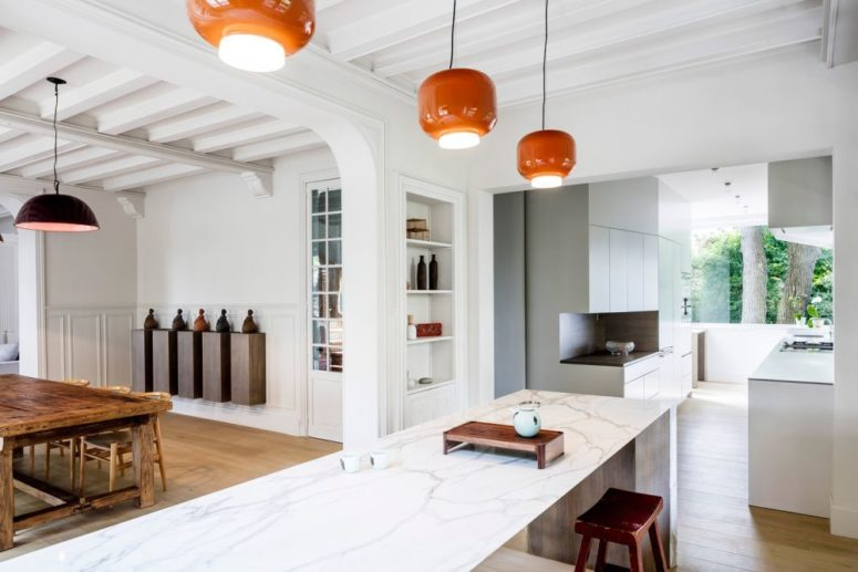 The kitchen features minimalist cabinets, a large kitchen island and a vintage dining set