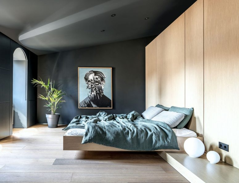The large master bedroom shows off much storage and a floating bed, dark walls and a large artwork