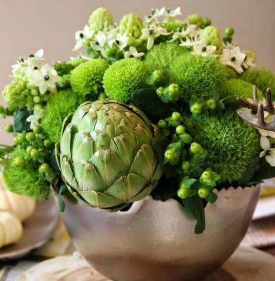 a chic fresh green Thanksgiving centerpiece of green blooms, berries, an artichoke and white flowers