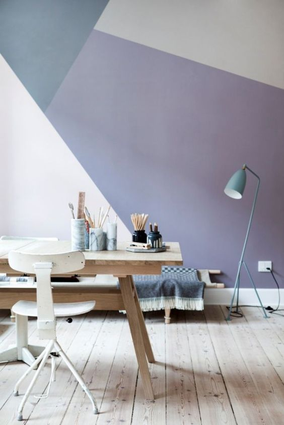 a gorgeous geometric color block wall with blush, lavender and grey plus a blue lamp