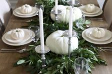 08 a neutral tablescape with white pumpkins, plates and candles and a fresh greenery table runner in the center