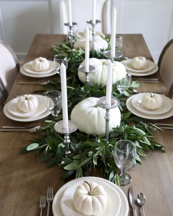 a neutral tablescape with white pumpkins, plates and candles and a fresh greenery table runner in the center
