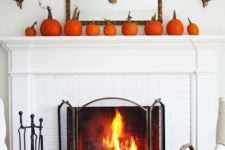 08 a simple rustic mantel with an arrangement of orange pumpkins and a wheat wreath on the mirror