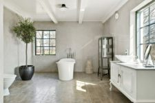 09 The bathroom is a large space with vintage furniture and a view plus a glass armoire
