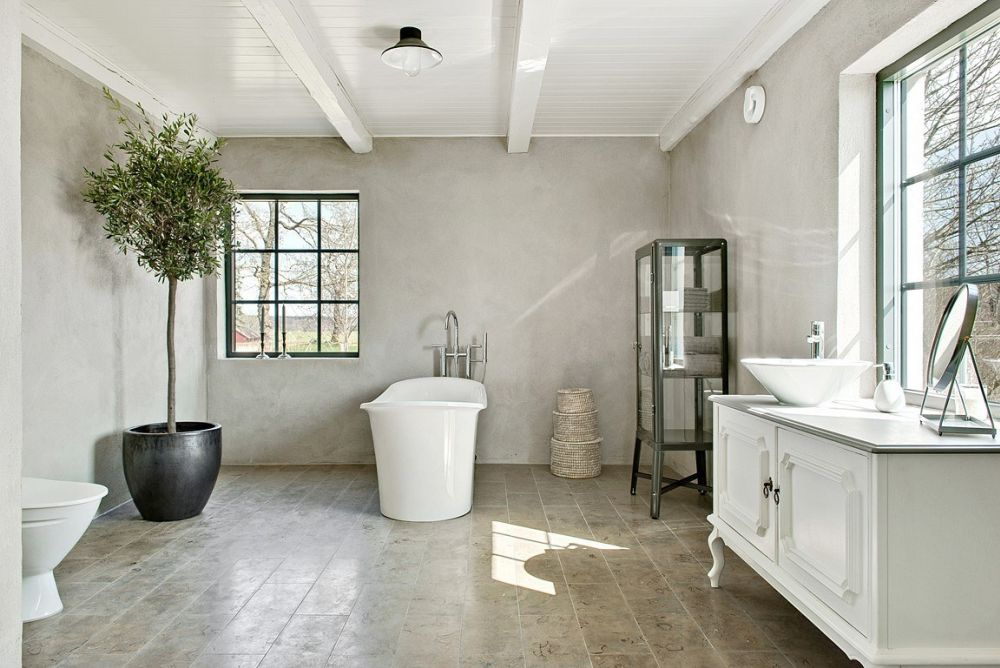 The bathroom is a large space with vintage furniture and a view plus a glass armoire