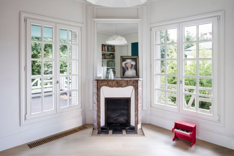The living room shows off a vintage fireplace and French windows
