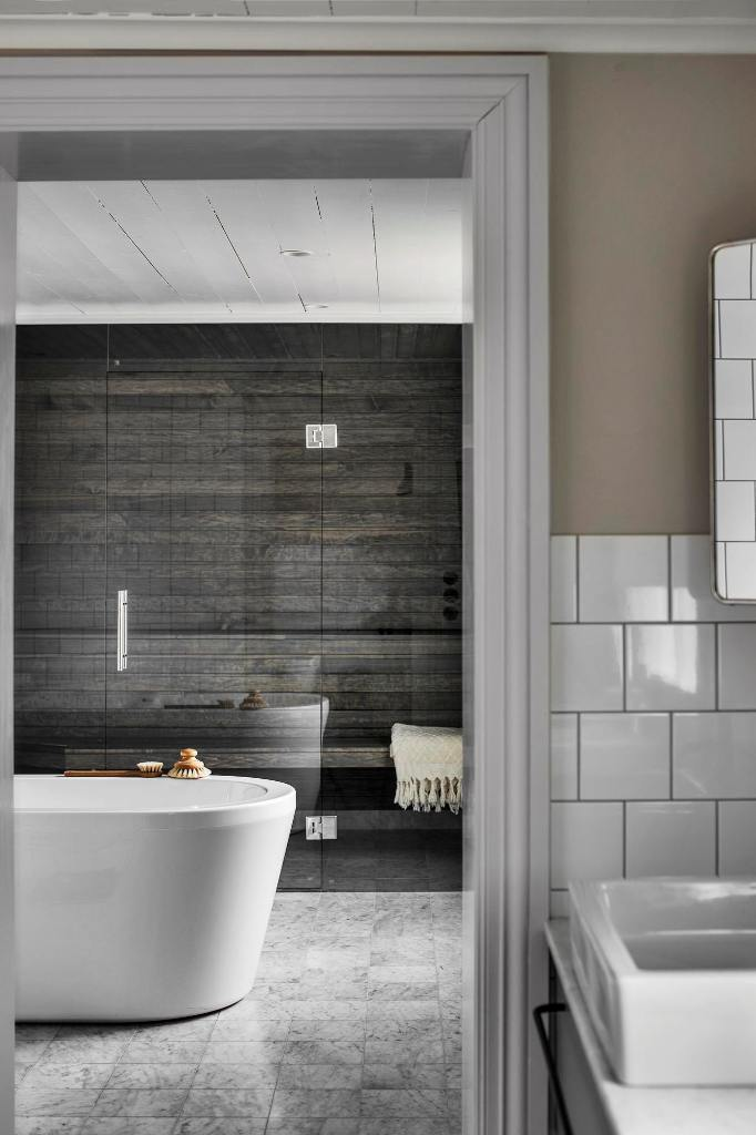 The second space is clad with weathered wood, there's a shower and a large bathtub