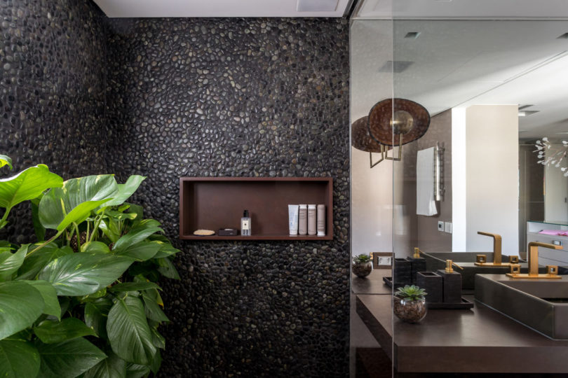 The shower clad with real pebbles and potted greenery make you feel like outdoors