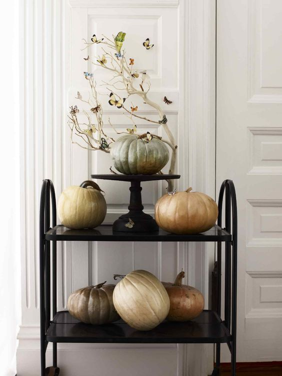 a black cart with pumpkins painted with pearly paint and whitewashed branches for Halloween