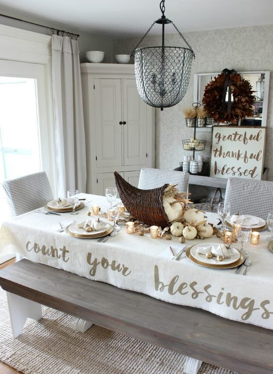 a rustic Thanksgiving table setting with neutral pumpkins, wheat and a cornucopia centerpiece