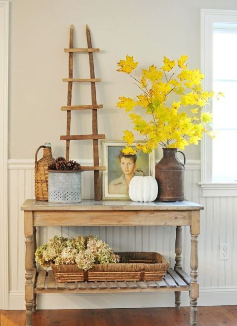 a rustic console with a fall leaf in a metal vase, pinecones, a fake pumpkin, hydrangeas in a wicker tray and artworks