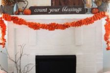 10 a large pallet, some orange pumpkins, an orange fabric garland and dried hydrangeas and firewood in the fireplace