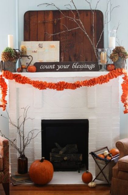 a large pallet, some orange pumpkins, an orange fabric garland and dried hydrangeas and firewood in the fireplace