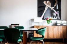 10 a mid-century modern dining room with emerald chairs with an oversized poster for a statement