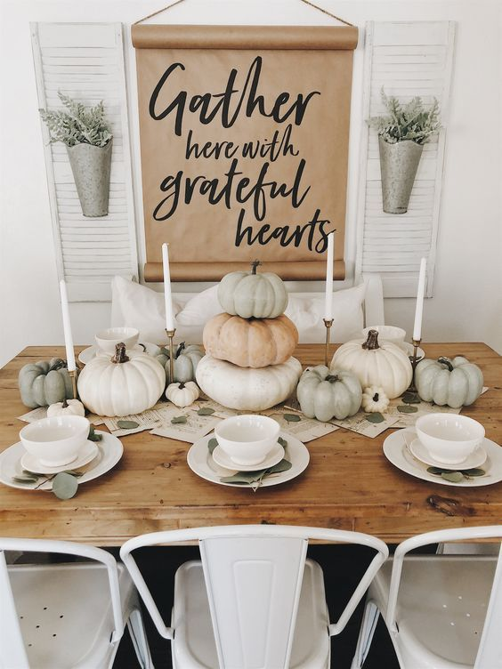 a natural table setting with candles and heirloom pumpkins plus a book page table runner and white porcelain