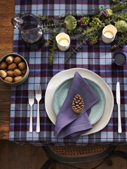 a plaid purple and burgundy tablecloth, a purple napkin, a blue plate and a purple glass pitcher look cozy