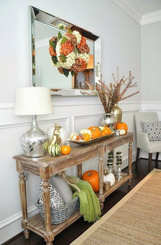 a rustic vintage console with real pumpkins, dried bloom wreaths, herbs, scarves and pillows