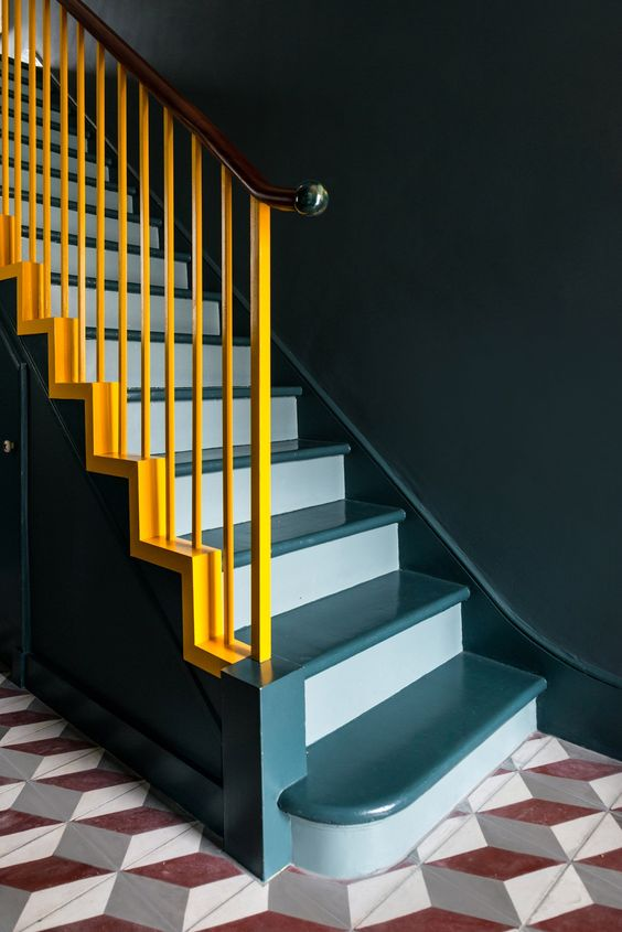 a staircase done in two shades of blue and spruced up with bold yellow railing for a contrast