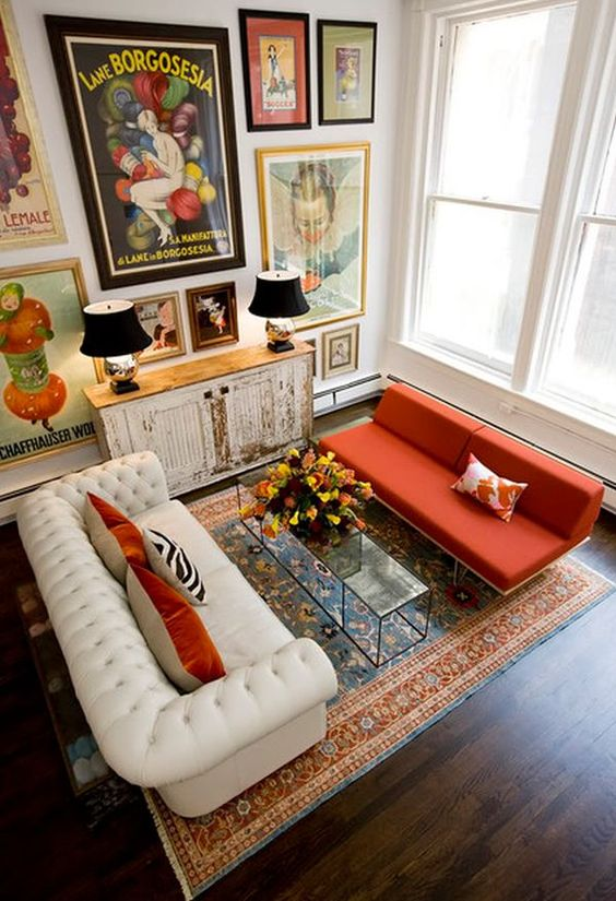 an eclectic living room with a bright gallery wall with vintage posters and artworks