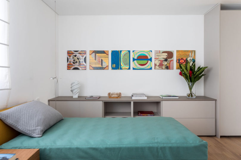 There's also a guest bedroom with a single bed and some storage items plus colorful artworks
