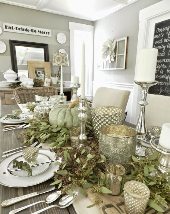 a cool table decorated with seeded eucalyptus, green pumpkins, mercury glass candle lanterns and candles