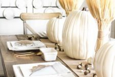 11 a neutral rustic table setting with large pumpkins, wheat, gilded cutlery and white plates, a wheat wreath on the wall