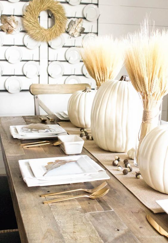 a neutral rustic table setting with large pumpkins, wheat, gilded cutlery and white plates, a wheat wreath on the wall