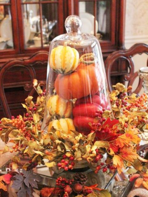 a rustic cloche display with fake pumpkins and peppers surrounded with foliage and berries for a vintage feel
