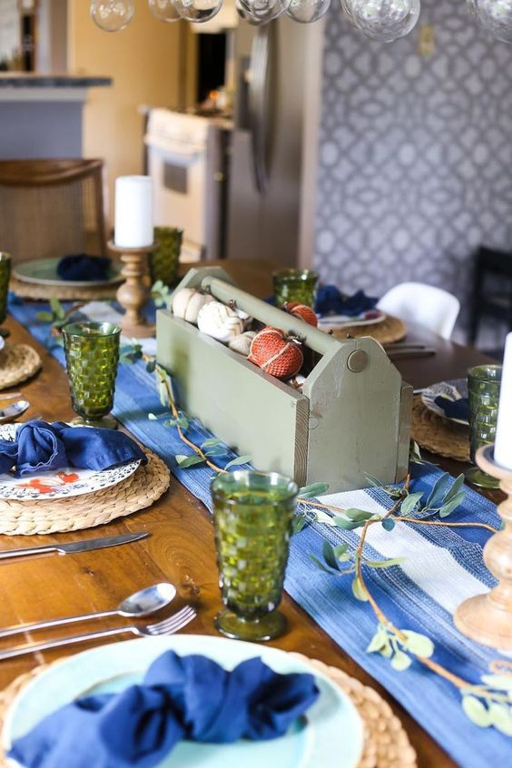 a simple and rustic Thanksgiving setting with a bold blu runner and napkins plus green glasses