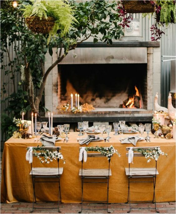 a very cozy table setting placed in a patio with a fireplace, which will keep you warm when it's getting later