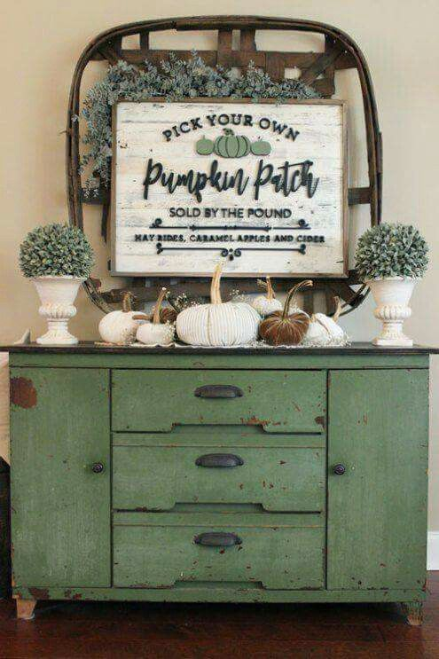 a vintage and rusty console with fabric pumpkins, faux greenery in pots and cool decor on the wall with a sign