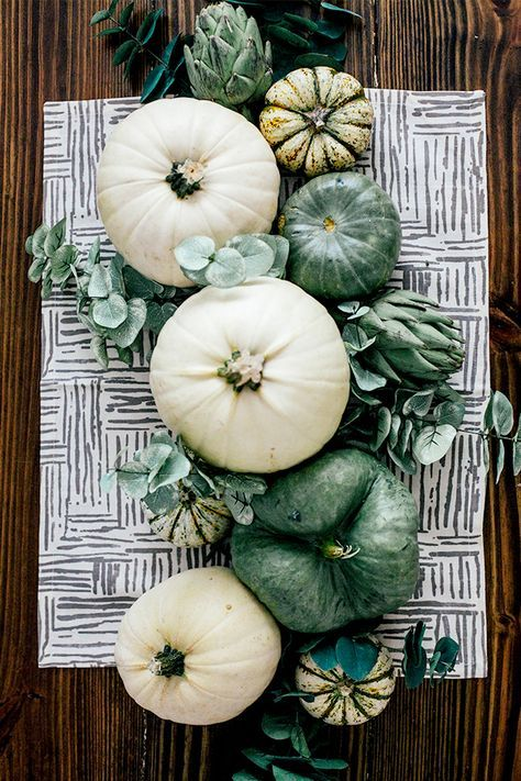a cute natural Thanksgiving centerpiece of white and green heirloom pumpkins and fresh eucalyptus