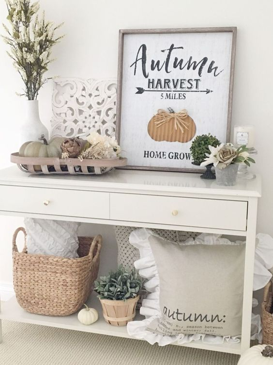 a simple console with faux pumpkins, a basket, a pillow, greenery and a fall sign plus fresh blooms
