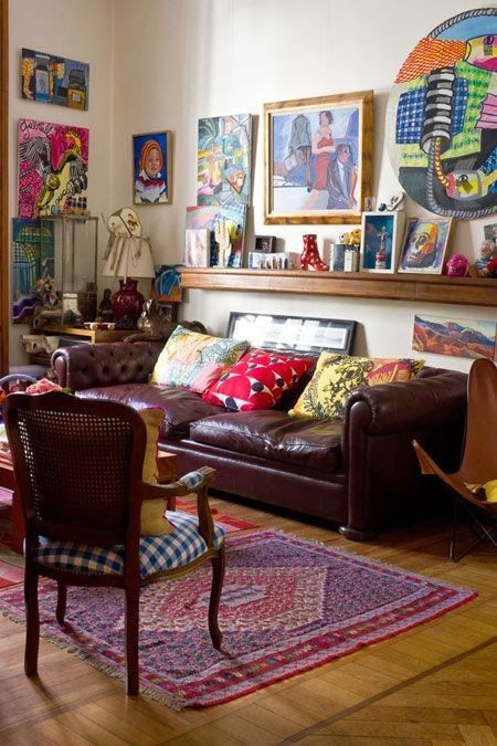 a traditional space spruced up with super bold and vibrant artworks and pillows and rugs that create a mood
