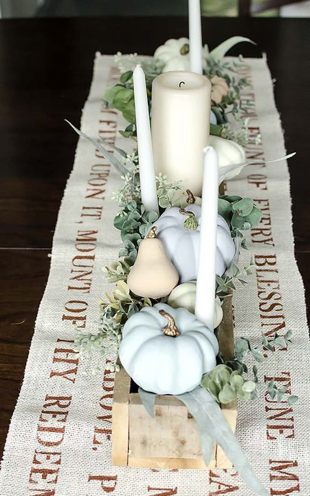 a chic neutral fall or Thanksgiving centerpiece of a wooden box, candles, greenery, faux pumpkins and pears