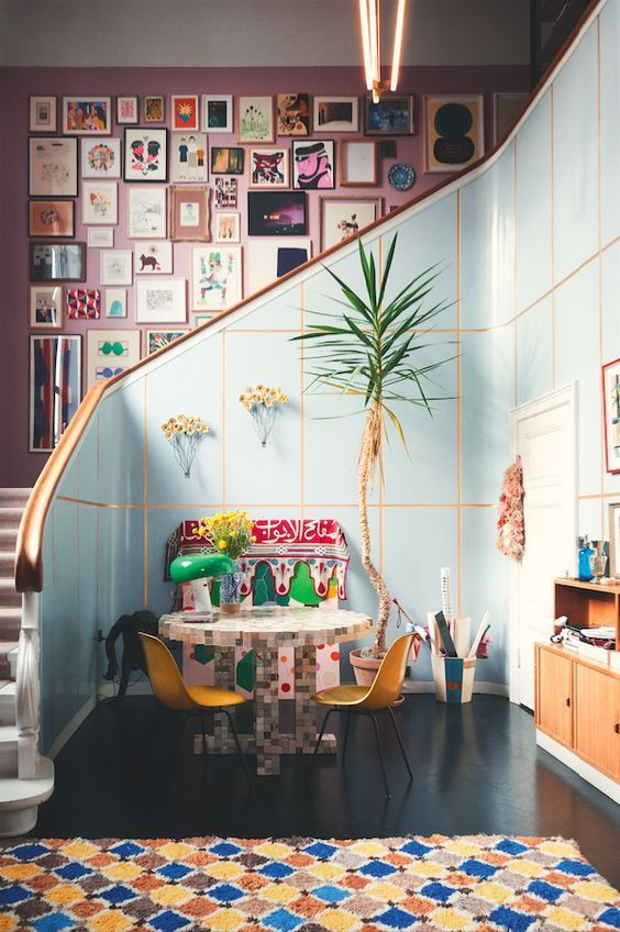 a colorful space and a pink wall that is completely covered with bright artworks for a bold touch