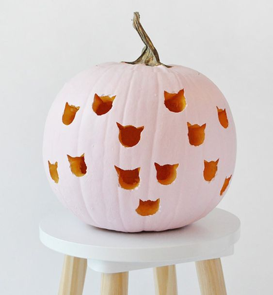a pink carved pumpkin with cat heads for Halloween decor and a girlish touch
