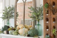 13 a rustic Thanksgiving mantel with various pumpkins, pinecones, greenery in bottles and leaves