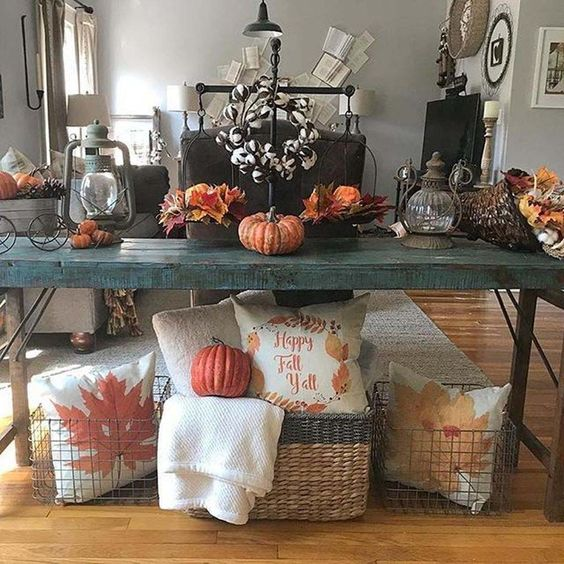 a teal rustic console with fall leaves, pumpkins, a cotton wreath and baskets with fall printed pillows