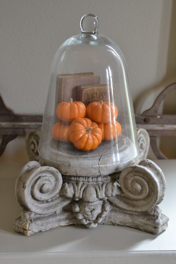 a vintage cloche with fake pumpkins and vintage books is a chic idea for farmhouse, vintage and rustic decor