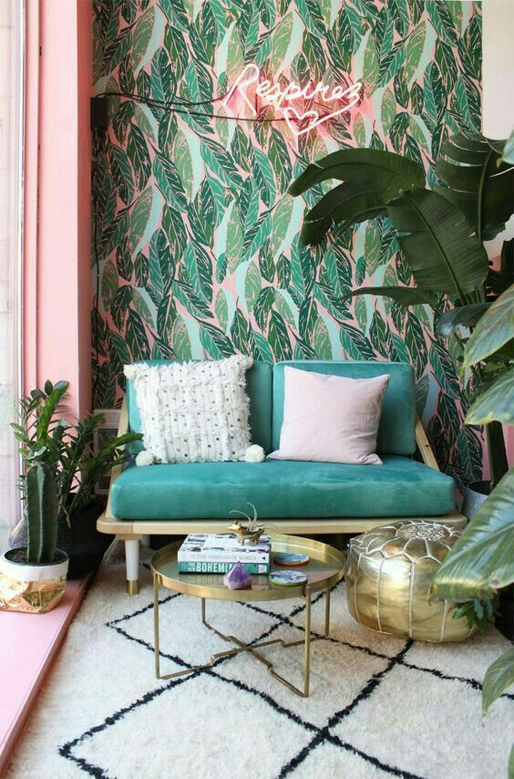 bold leaf printed wallpaper is paired with a simple and neutral printed rug and a polka dot pillow