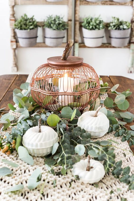 a chic Thanksgiving centerpiece with a macrame table runner, greenery, a candle in a copper candle holder
