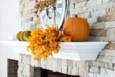 14 a rustic mantel with fall elaves, moss balls, pumpkins and fruits on the branches is suitable for both fall and Thanksgiving